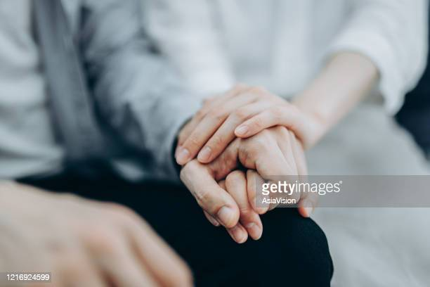 cropped shot of a young couple sitting on sofa compassionately holding hands in self isolation during covid-19 health crisis - holding hands stock pictures, royalty-free photos & images