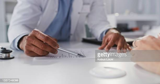 cropped shot of an unrecognizable doctor sitting and reading test results with his patient during a consultation in his clinic - unrecognisable person stock pictures, royalty-free photos & images