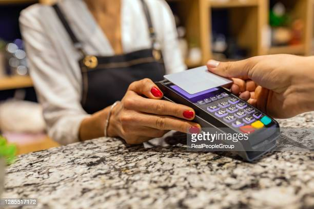cropped shot of an unrecognizable man paying for his purchase by card - paying stock pictures, royalty-free photos & images