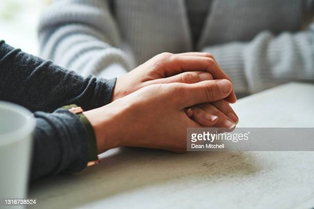 cropped shot of an unrecognizable nurse sitting with her senior patient at home and holding her hand - emotional support stock pictures, royalty-free photos & images