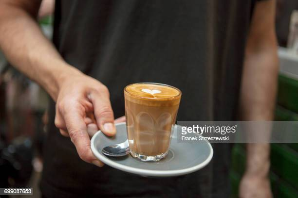 Cropped shot of barista holding glass of coffee in cafe