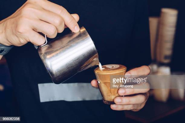cropped shot of barista making cappuccino/latte by pouring milk in coffee cup for make latte art. - espresso stock photos and pictures