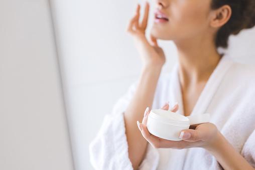 cropped shot of beautiful woman in bathrobe applying face cream 923660962