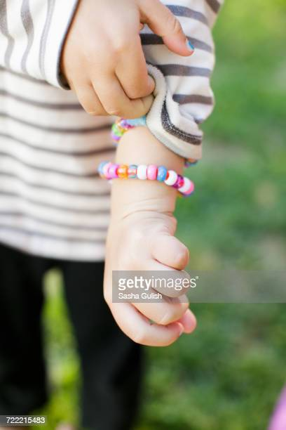 cropped shot of boy holding sleeve and showing bracelet - hands in her pants fotografías e imágenes de stock