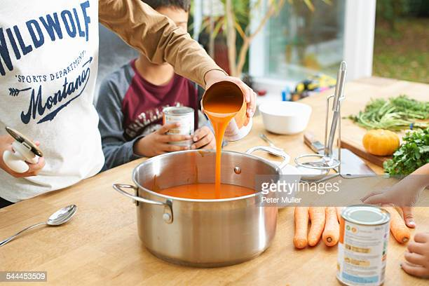 cropped shot of boy pouring tin of tomato soup into saucepan - saucepan stock pictures, royalty-free photos & images
