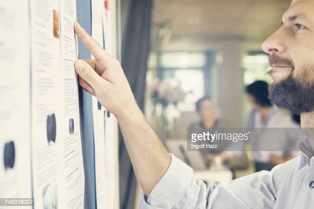 Cropped shot of businessman looking at office notice board