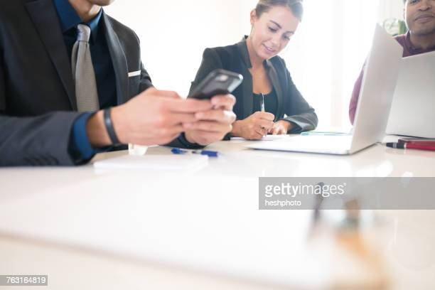 cropped shot of businessman looking at smartphone during meeting - heshphoto stock pictures, royalty-free photos & images