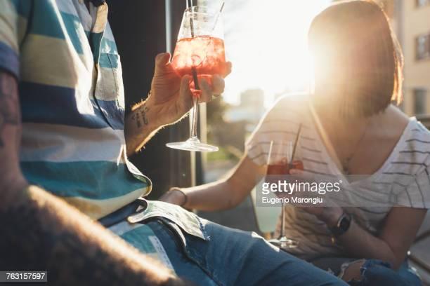 Cropped shot of couple sitting outside sunlit sidewalk cafe having cocktails