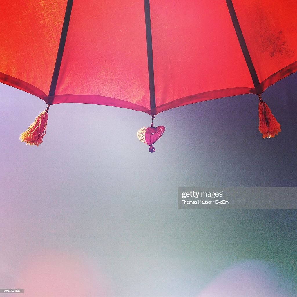Cropped Shot Of Decorations Hanging Umbrella Against Clear Sky Stock Photo