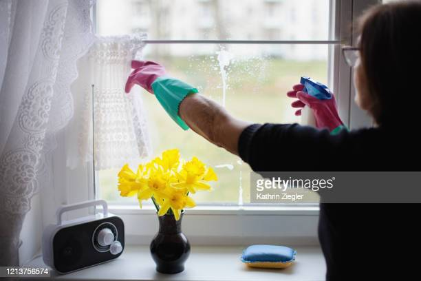 cropped shot of elderly woman partially cleaning window with cleaning spray, removing fingerprints - radio stock pictures, royalty-free photos & images