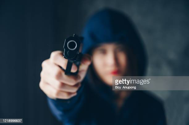 cropped shot of female criminal (or thief) wearing hood and aiming handgun to the target. - weapon stock pictures, royalty-free photos & images