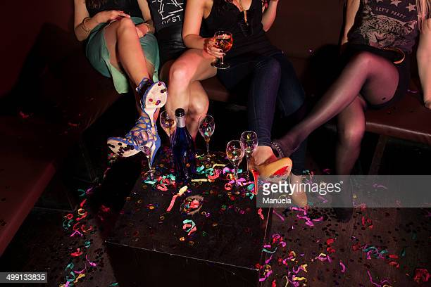 cropped shot of female mini skirted friends in nightclub - legs and short skirt sitting down stock photos and pictures