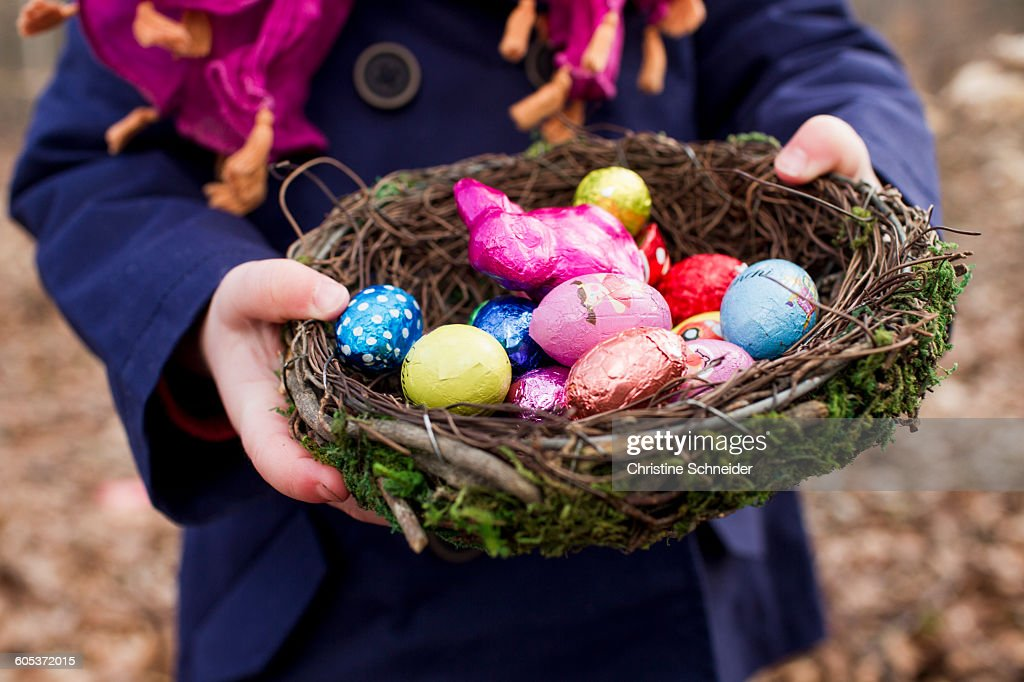 Cropped shot of female toddler holding basket nest of easter eggs in forest : Stock Photo