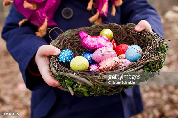 cropped shot of female toddler holding basket nest of easter eggs in forest - easter egg stock pictures, royalty-free photos & images