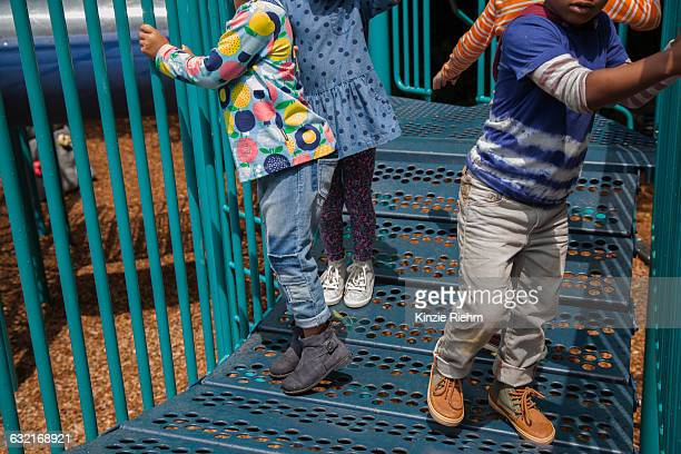 cropped shot of four boys and girls playing on climbing frame in playground - 6 7 anni foto e immagini stock