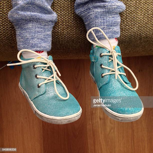 Cropped shot of legs of child wearing turquoise shoes