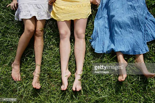 Cropped shot of legs of three teen girls lying on the grass