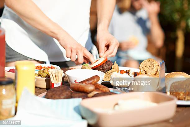 Cropped shot of male hands preparing burger at rooftop party