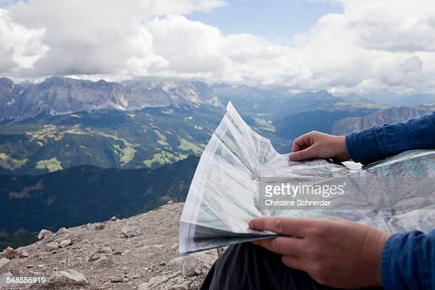 cropped shot of male hiker on top of mountain holding map, peitlerkofel, south tyrol, italy - karte navigationsinstrument stock-fotos und bilder