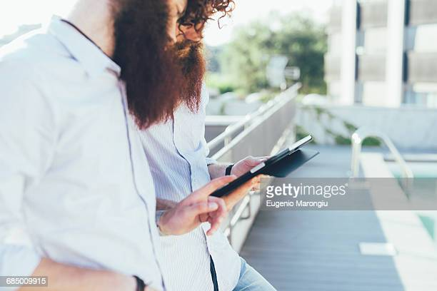 Cropped shot of male hipster twins using digital tablet on apartment roof terrace