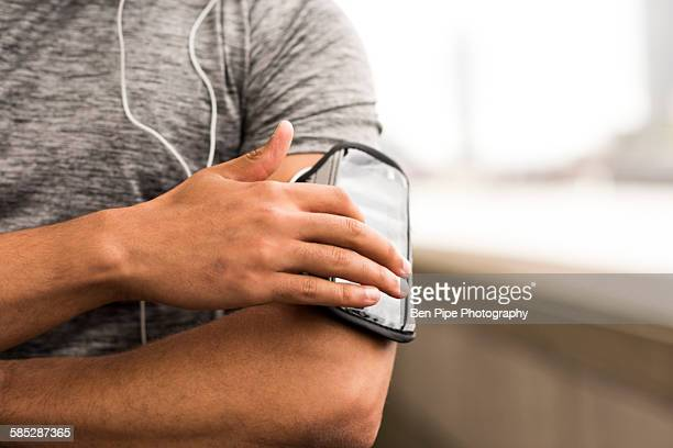 Cropped shot of male runner choosing music on smartphone armband
