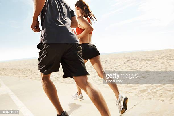 Cropped shot of man and woman running on beach