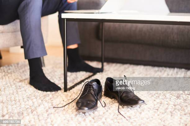 Cropped shot of mans legs and feet in living room