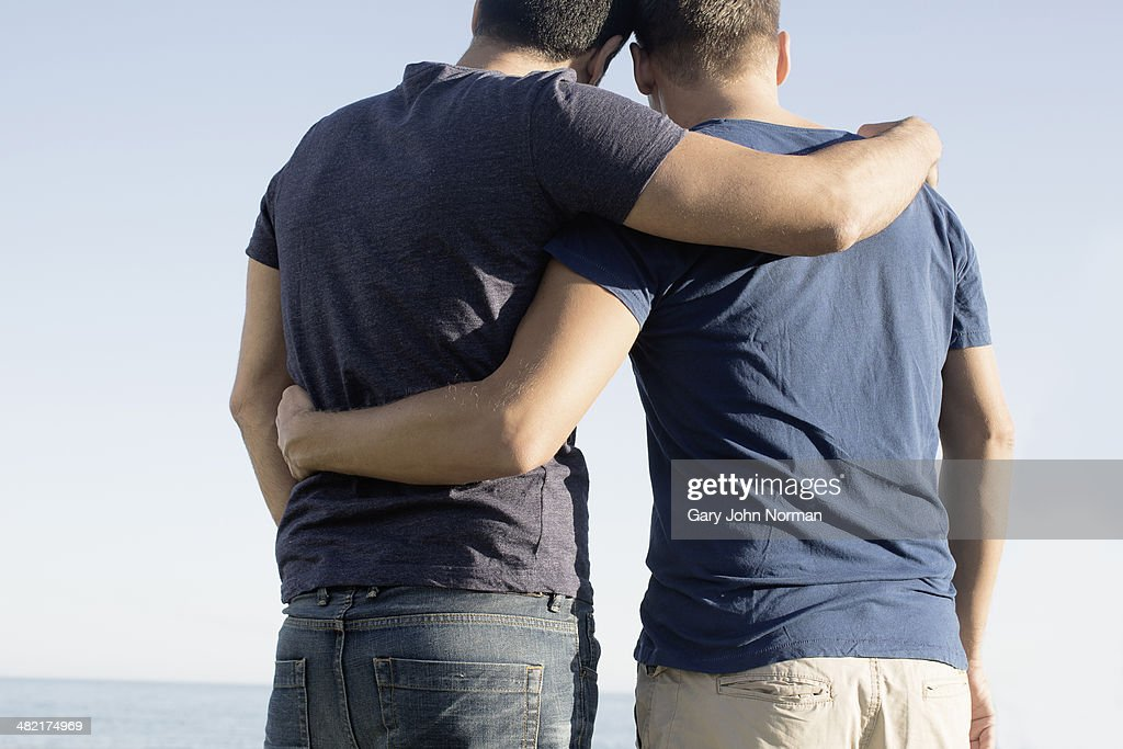 Cropped shot of mature male couple with arms around each other at coast : ストックフォト