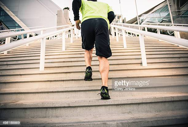 Cropped shot of mature male runner training on steps
