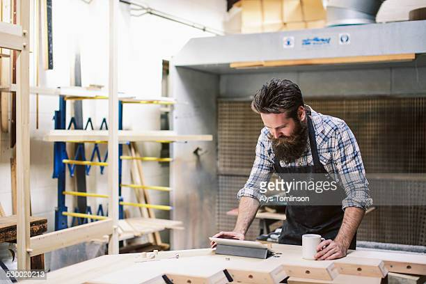 Cropped shot of mid adult craftsman using digital tablet in organ workshop