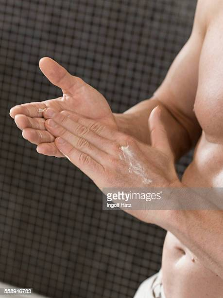Cropped shot of muscular man in bathroom rubbing in hand cream