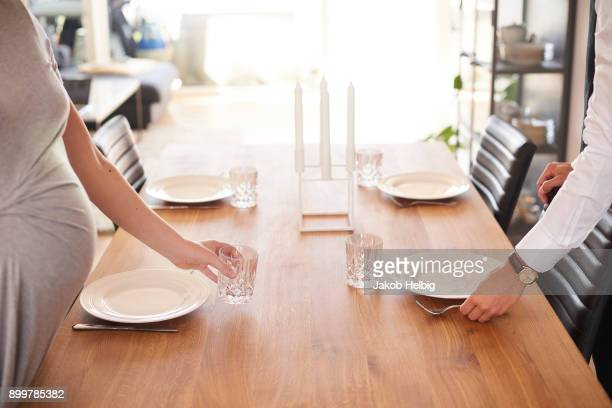 Cropped shot of pregnant couple laying dining table