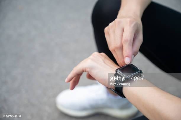 cropped shot of runner woman kneeling while checking health status and fitness progress on her smart watch. - smart watch stock pictures, royalty-free photos & images
