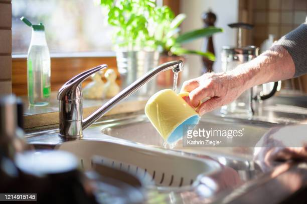 cropped shot of senior man doing the dishes - 皿洗い ストックフォトと画像