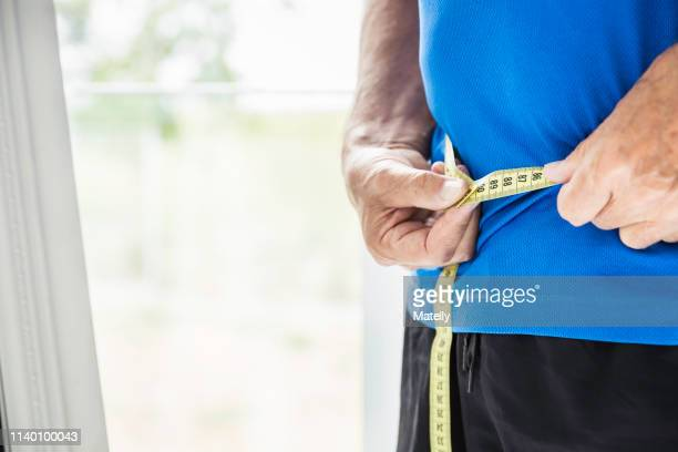 cropped shot of senior man measuring his waist - weight loss stock pictures, royalty-free photos & images