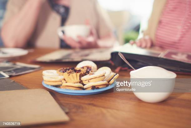 cropped shot of senior women at table with sugar bowl, biscuits and photo album - sugar bowl crockery stock photos and pictures
