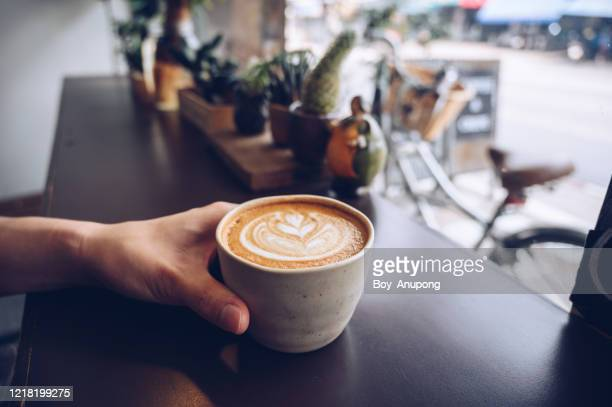 cropped shot of someone hand with a cup of hot latte coffee on the table nearly window. - coffee stock pictures, royalty-free photos & images