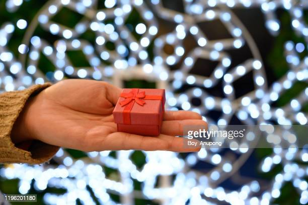 cropped shot of someone hand with a small red wrapped gift box. - ギフトショップ ストックフォトと画像
