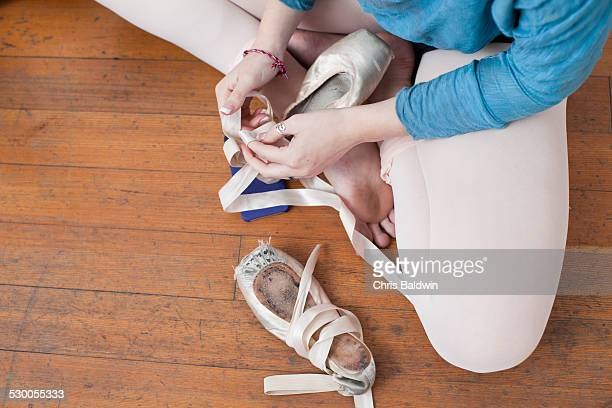 Cropped shot of teenage girl tying ballet slippers in ballet school