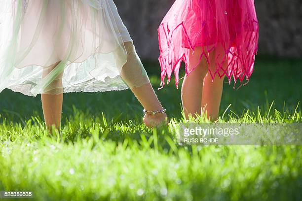 Cropped shot of the legs of two girls in fairy costume in garden