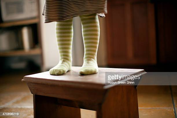 Cropped shot of toddler's legs standing on stool in kitchen