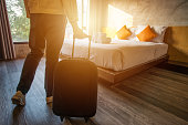 Cropped shot of tourist woman pulling her luggage to her hotel bedroom after check-in.