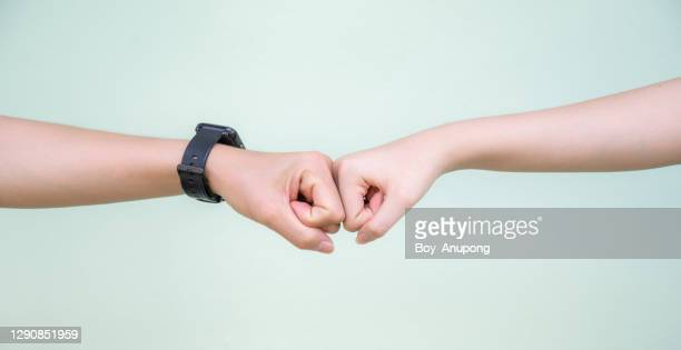 cropped shot of two people bump their fists together (or knuckle bump) for greeting. - friendly match stock pictures, royalty-free photos & images