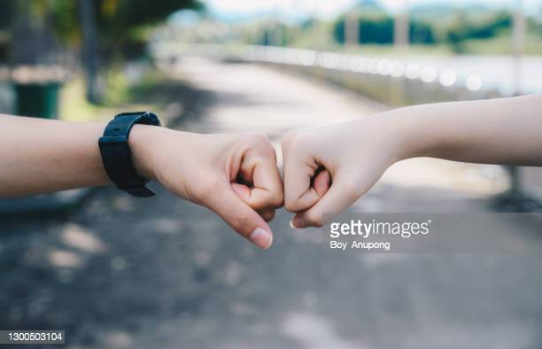 cropped shot of two people bump their fists together (or knuckle bump) for greeting. - bumpy stock pictures, royalty-free photos & images