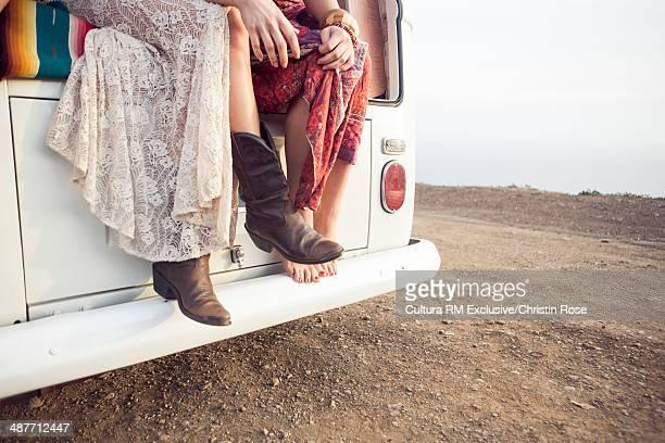 Cropped shot of two women sitting on camper van
