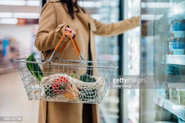 cropped shot of woman carrying shopping basket and shopping groceries in supermarket - supermarket stock pictures, royalty-free photos & images