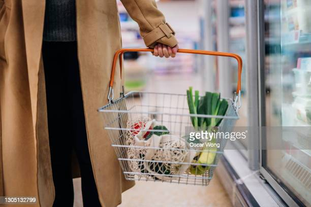 cropped shot of woman carrying shopping basket and shopping groceries in supermarket - close up stock pictures, royalty-free photos & images