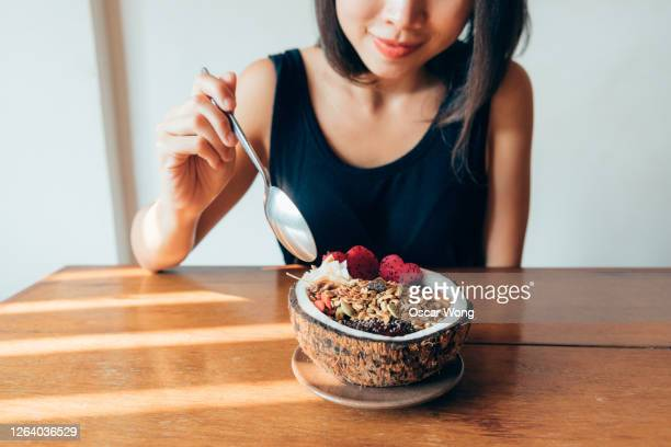 cropped shot of woman eating superfood smoothie bowl - young women stock pictures, royalty-free photos & images