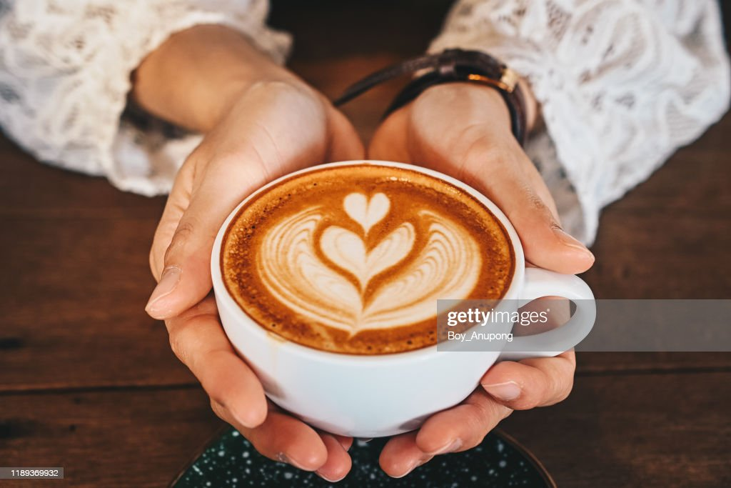 Cropped shot of woman hands holding a cup of hot latte coffee in her hands. : Stockfoto
