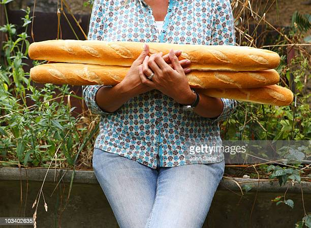 cropped shot of woman holding baguettes